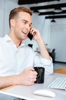 Giovane uomo d'affari allegro che beve caffè e parla al telefono cellulare in ufficio