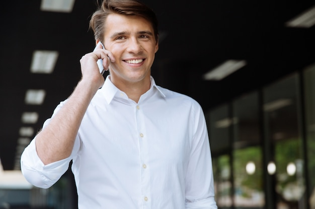 Allegro giovane imprenditore sorridente e parlando al cellulare per strada