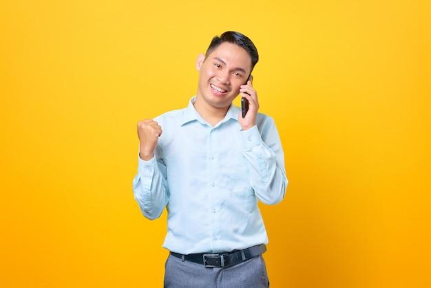 Giovane uomo d'affari allegro che parla sullo smartphone e si rallegra del divertimento su sfondo giallo