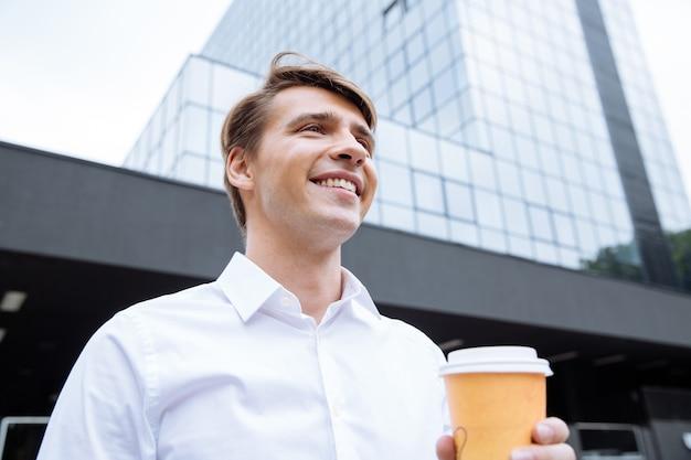 Allegro giovane imprenditore utilizza lo smartphone vicino al centro business