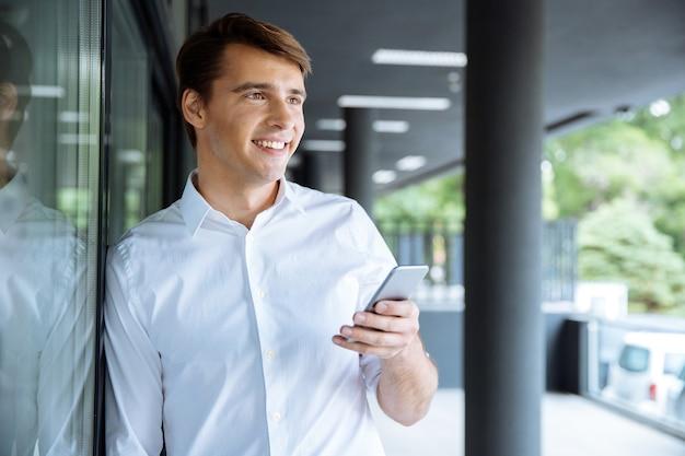 Allegro giovane imprenditore in attesa e utilizzando il telefono cellulare