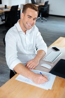 Giovane uomo d'affari allegro che scrive alla tavola sul posto di lavoro