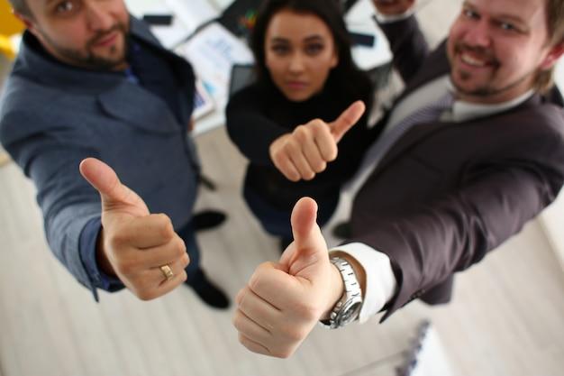 I giovani imprenditori allegri hanno risultati di successo che mostrano grandi dita