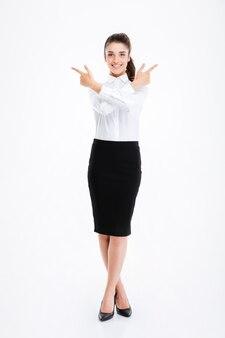 Allegra giovane imprenditrice in piedi e indicando via con entrambe le mani sul muro bianco