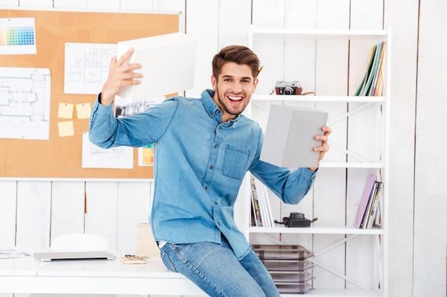 Allegro giovane uomo casual che tiene scatole mentre è seduto alla scrivania in ufficio