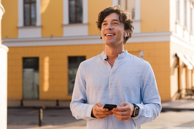 Allegro giovane uomo casual tenendo il telefono cellulare