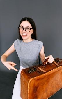 Allegro giovane donna caucasica azienda bagagli valigia su sfondo grigio