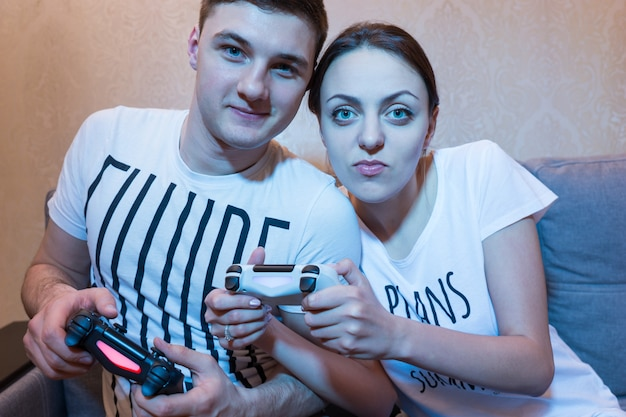Allegra giovane coppia di ragazzo e ragazza che giocano a videogiochi seduti sul divano davanti alla tv a casa in un'atmosfera rilassata