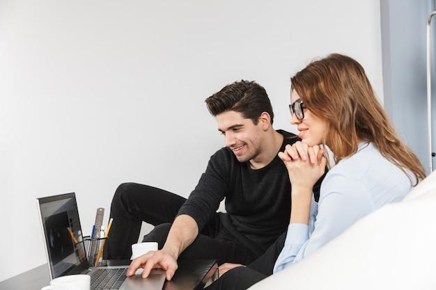 Allegro giovane coppia di colleghi che lavorano insieme in ufficio, concetto di lavoro di squadra di co-working, utilizzando il computer portatile