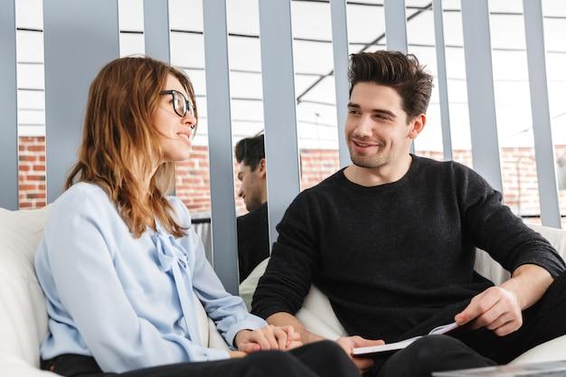 Allegro giovane coppia di colleghi che lavorano insieme in ufficio, concetto di lavoro di squadra di co-working