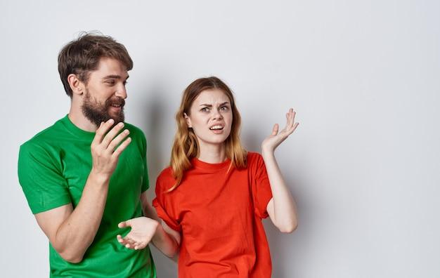 Allegro giovane coppia in t-shirt colorate emozioni studio stile di vita sfondo isolato.