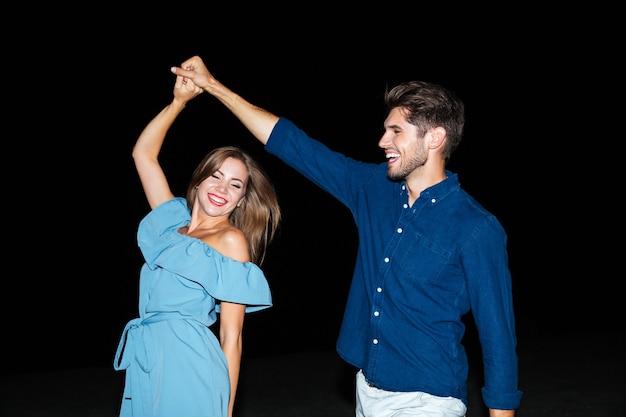 Allegra giovane coppia che balla e ride sulla spiaggia di notte