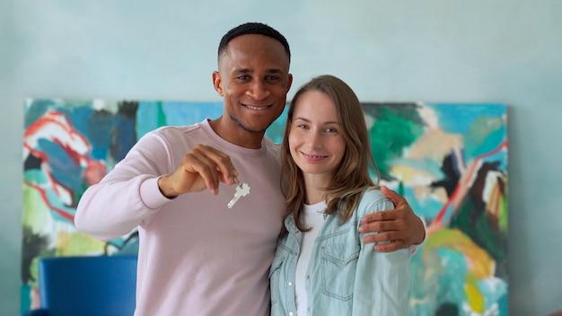 Giovani coppie allegre che tengono le chiavi e sorridere mentre levandosi in piedi nella loro nuova casa