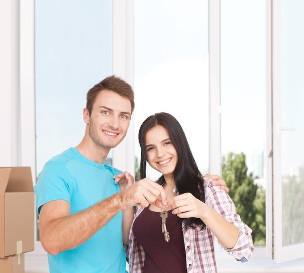 Giovani coppie allegre che tengono le chiavi della loro nuova casa