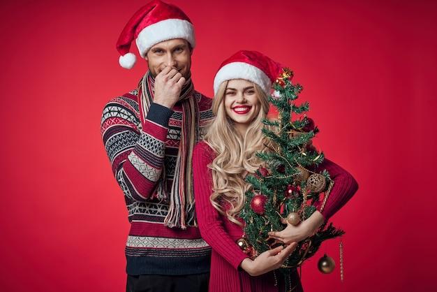 Allegro giovane coppia capodanno decorazione dell'albero sfondo rosso