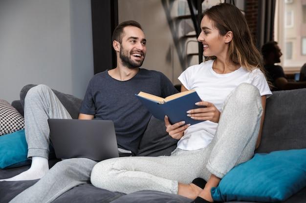 Allegro giovane coppia rilassante sul divano a casa