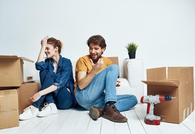 Allegro giovane coppia in camera sul divano con scatole
