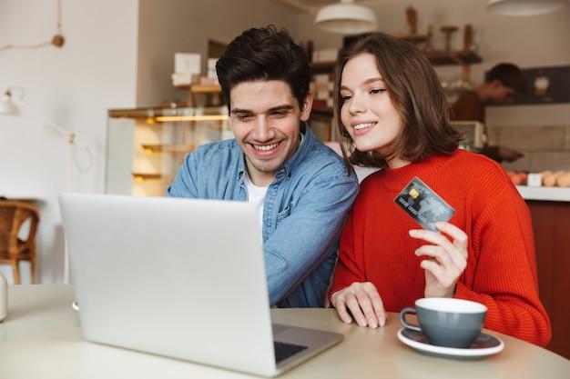 Giovani coppie allegre che mostrano la carta di credito