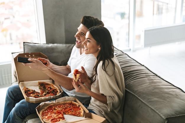 Allegro giovane coppia seduta su un divano a casa, mangiare la pizza