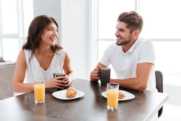 Giovani coppie allegre che si siedono e che bevono caffè al tavolo in cucina