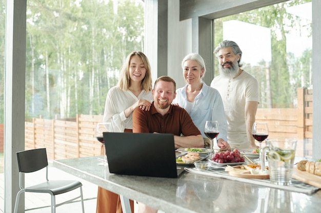 Allegro giovane coppia seduta sul divano e agitando le mani al computer portatile durante la chat tramite collegamento video nel soggiorno del cottage