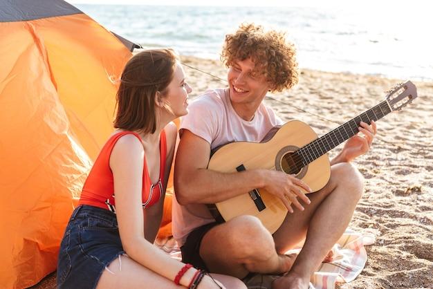 Allegro giovane coppia seduti insieme in spiaggia, campeggio, suonare la chitarra