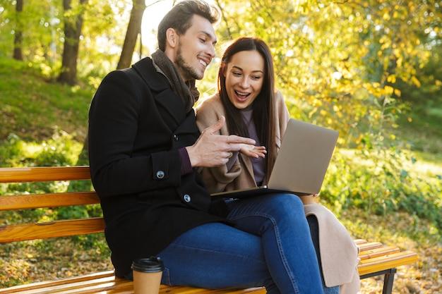 Una giovane coppia allegra che trascorre del tempo divertente al parco in autunno, seduta su una panchina, usando il laptop