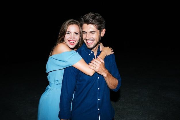 Allegra giovane coppia stading e abbracciando sulla spiaggia di notte