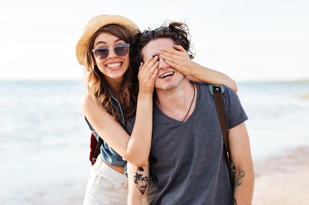 Allegro giovane coppia in piedi e divertirsi sulla spiaggia