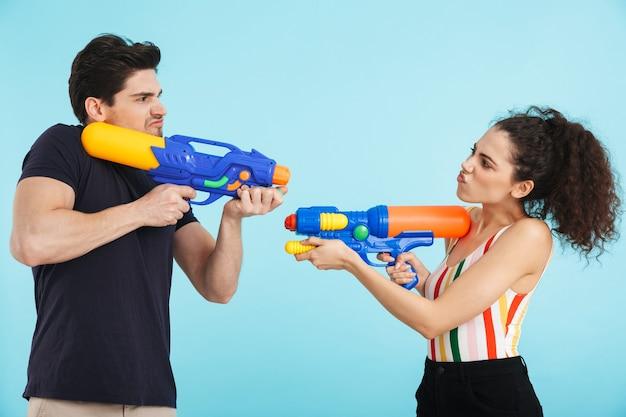 Allegra giovane coppia in piedi isolata, divertendosi con pistole ad acqua