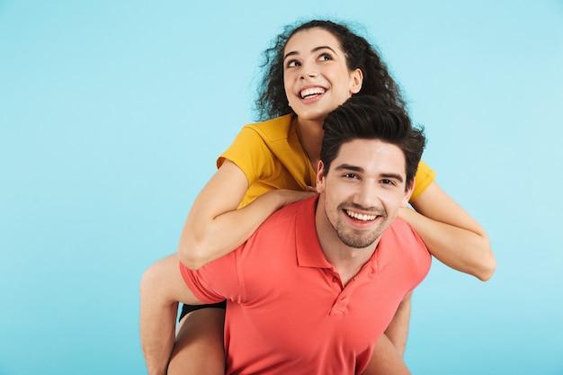 Allegra giovane coppia in piedi isolata, cavalcata sulle spalle