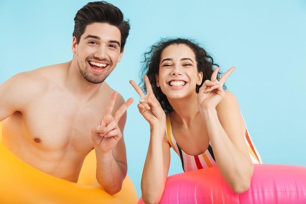 Allegra giovane coppia in piedi isolata, indossando un anello gonfiabile