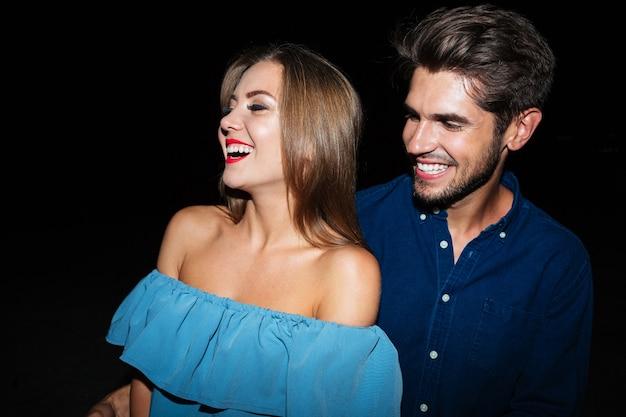 Allegra giovane coppia in piedi e ridendo insieme di notte