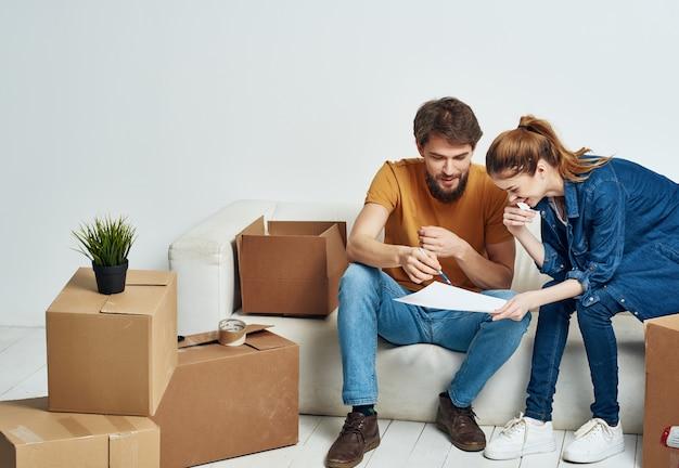Giovani coppie allegre che disimballano le scatole che si trasferiscono in un nuovo stile di vita in appartamento