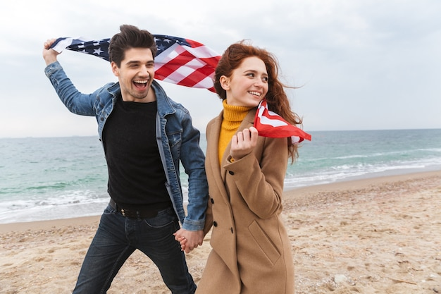 Giovani coppie allegre che camminano sulla spiaggia, portando la bandiera americana