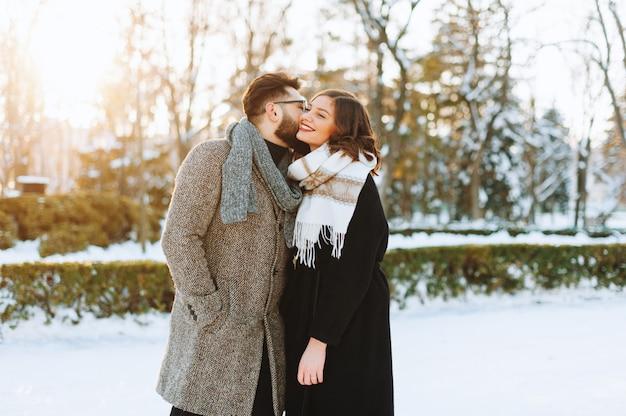 Giovani coppie allegre, in cui l'uomo bacia la ragazza sulla guancia nel parco.