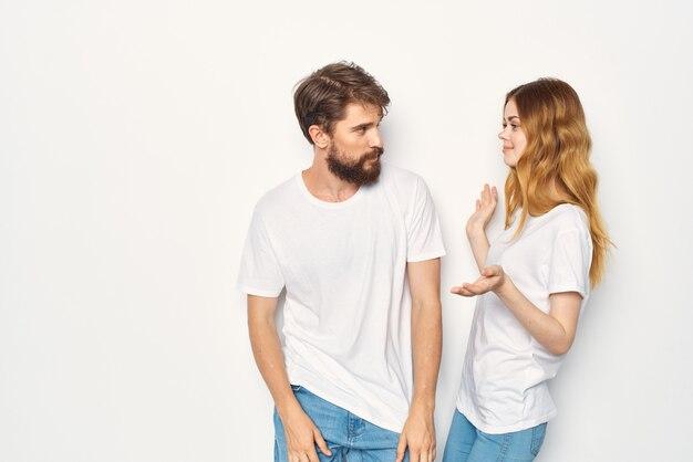 La giovane coppia allegra in magliette bianche abbraccia lo stile di vita dell'amicizia
