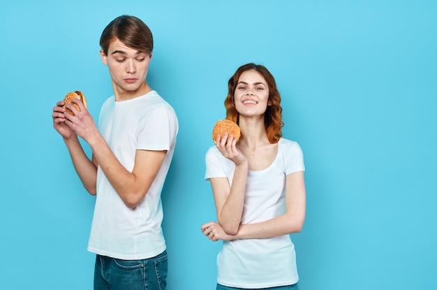 Giovani coppie allegre in magliette bianche che si divertono con gli hamburger del fast food