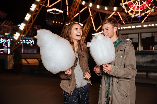 Allegra giovane coppia con zucchero filato in piedi e ridendo nel parco divertimenti