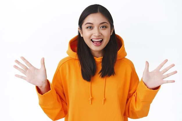 Allegra giovane donna asiatica carina in maglione arancione che cattura qualcosa, stringe la mano di lato per raccontare una storia incredibile con eccitazione, in piedi sul muro bianco sorridente