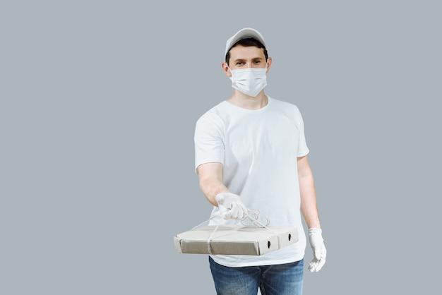 Allegro giovane uomo di consegna in una maschera e guanti con scatole per pizza su un grigio