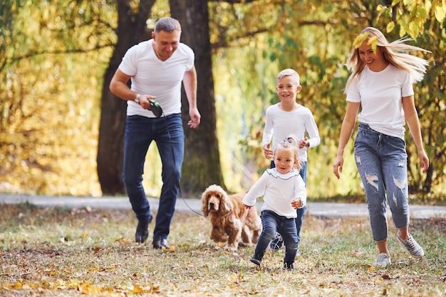 La giovane famiglia allegra fa una passeggiata insieme in un parco autunnale.