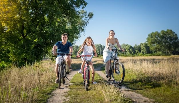 Giovane famiglia allegra che guida sulle biciclette al prato. concetto di sport familiare