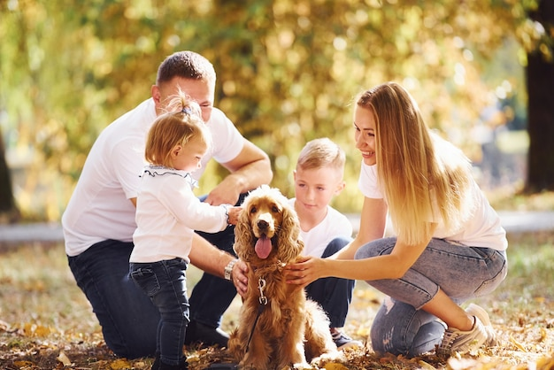 La giovane famiglia allegra con il cane si riposa insieme in un parco autunnale.