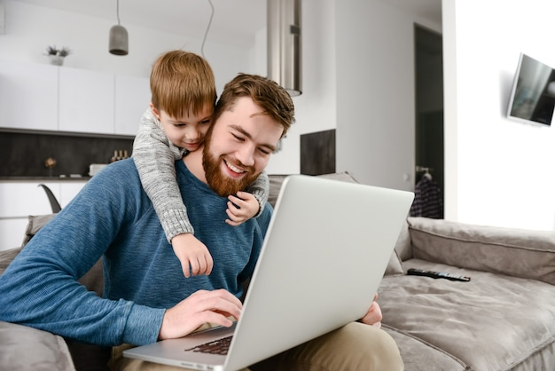 Allegro giovane padre con figlio carino utilizzando il computer portatile al chiuso. guarda il portatile.