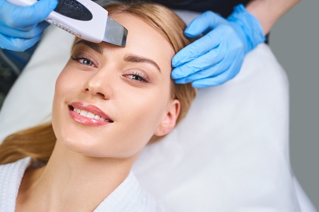 La giovane donna allegra è sdraiata sul divano mentre si fa il viso da un cosmetologo con un dispositivo digitale