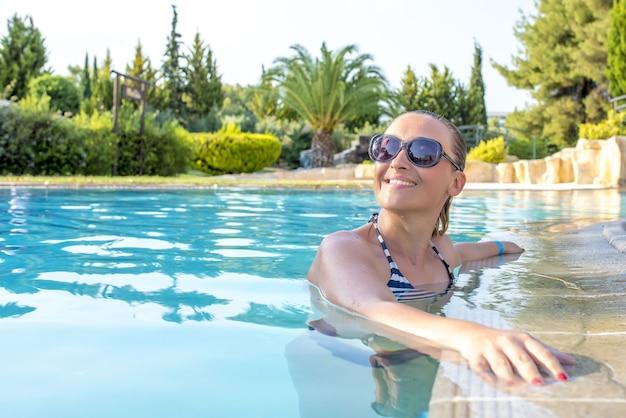 Allegra giovane donna con occhiali da sole in una piscina sotto la luce del sole di giorno