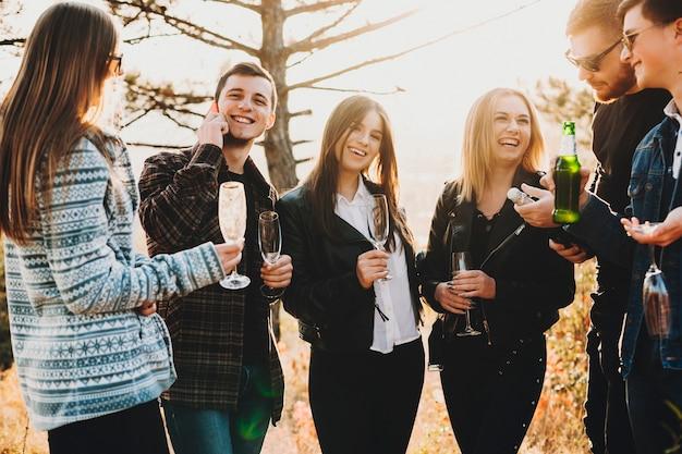 Giovani amici allegri che sorridono e bevono birra e champagne mentre levandosi in piedi insieme nella campagna meravigliosa