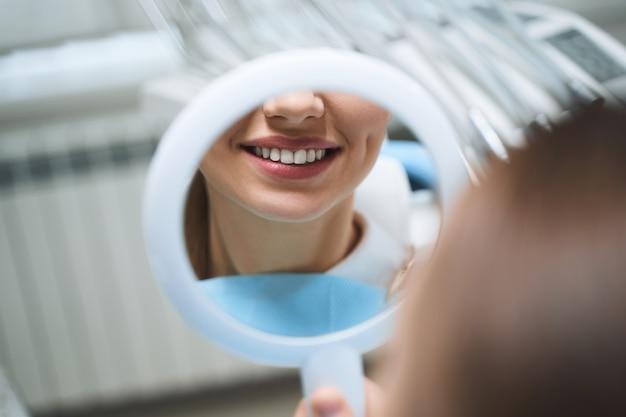 La ragazza allegra sta visitando la clinica dentale e sta guardando il riflesso del suo sorriso dopo il trattamento