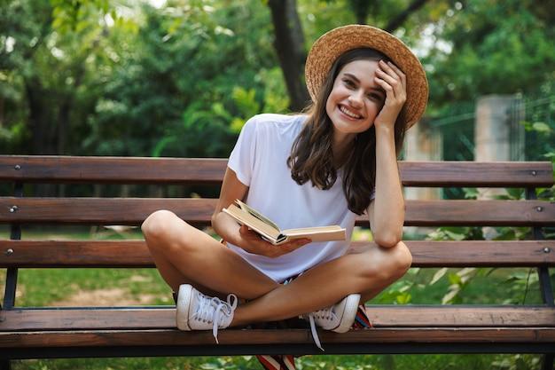 Ragazza allegra che legge un libro mentre era seduto al parco all'aperto